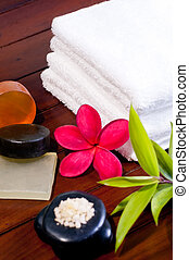 Spa concept with zen stone, bath salt, soap and a red flower