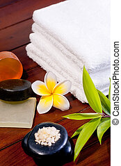 Spa concept with zen stone, bath salt, soap and a yellow frangipani flower on wooden background