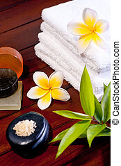 Spa concept with zen stone, bath salt, soap and  yellow flowers on wooden background