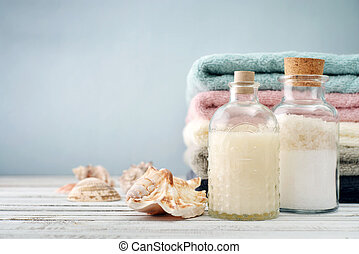 Bottles with shampoo and sea salt with towels on light background
