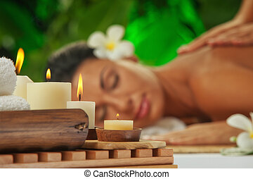 spa. focused on candles - portrait of young beautiful woman...