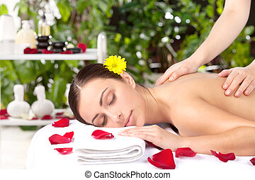 Spa girl. Beautiful young woman with flower in head lying on front while massage therapist massaging her back