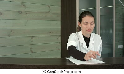 Spa manager filling in form and greeting customers at the reception desk