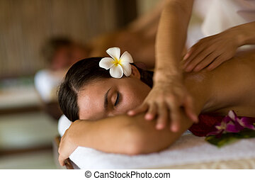 A young woman having massage in tropical spa