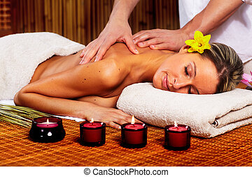 Spa massage. - Beautiful young woman in a day spa getting ...