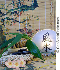 Massage items against a painted bamboo background for spa or feng-shui theme with aromatherapy candle, massage tools, therapy stones, bamboo leaves and plumeria flowers.