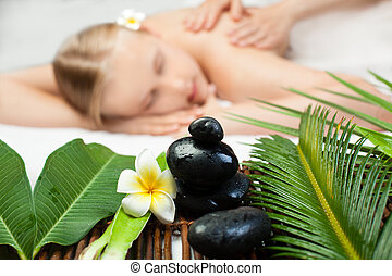 Spa massage objects in focus. Beautiful young woman getting spa massage