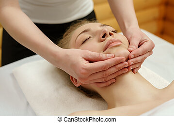 Spa. Massage therapist massaging client's chin