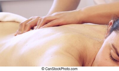 Close-up of woman relaxing during back massage lying on massage table at spa salon