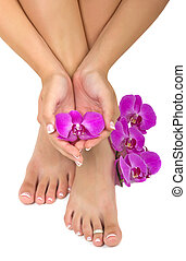 Pedicured feet and manicured hands with beautiful orchids