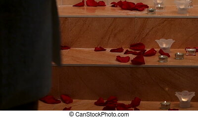Spa petals flowers and candels. Woman walking steps in bathroom.