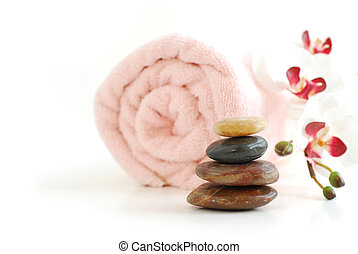 Spa - Pink rolled up towel with a stack of massage stones...