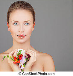 Spa Portrait of Perfect Woman with Beautiful Face,  Natural Makeup and Bright Colorful Flowers on Gray Background