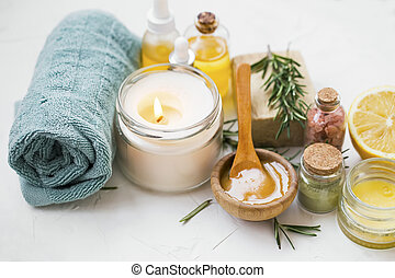 Spa products with candle, towels, manuka honey, oils, clay, bath salt, salve balm, spa setting with natural products for skincare treatments