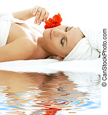 beautiful lady with red flower on white sand