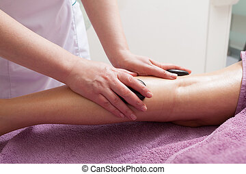 Day-spa. Therapist in work and female leg of customer. Young woman relaxing in healthy beauty spa salon. Girl having hot stone massage. Indoor. Bodycare and relax.