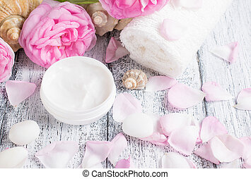 Spa salon with cream, towel and roses on the wooden board