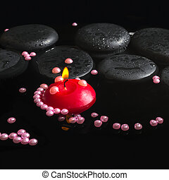 spa setting of orchid cambria flower on zen stones with drops, p