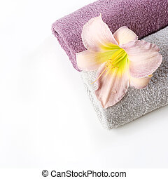 Spa setting of towel, pink flower isolated on white. Copy space. Square image.