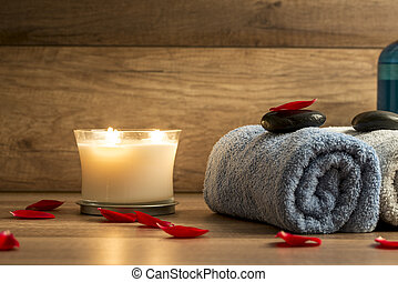 Spa setting with a rolled blue towel, romantic candle and...