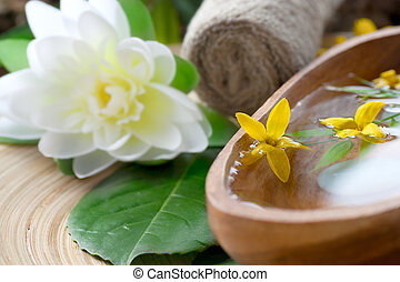 Spa setting with flower and towel on wooden background.