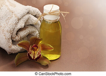 Spa setting with orchid, towel and massage oil