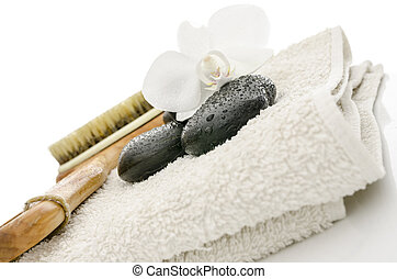 Spa setting with massage stones, brush, flower and a towel