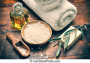 Spa setting with natural olive soap and sea salt on wooden...