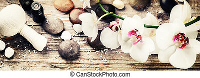 Spa setting with white orchid, herbal massage ball and...