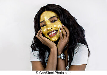 Spa, skin care, female facial treatment. Beauty close up portrait of joyful African woman with golden peel off facial mask touching her face and smiling to camera. Isolated on white background