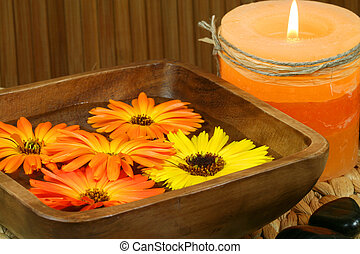 Orange marigold flowers floating in wooden bowl, burning candle and stones. Spa still life