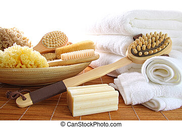 Spa still life of assorted bath brushes and sponges, soap towels on white