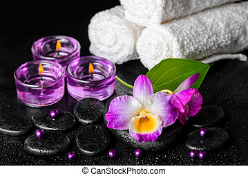 spa still life of purple orchid dendrobium, leaf with dew, towels, candles and pearl beads on black zen stones,