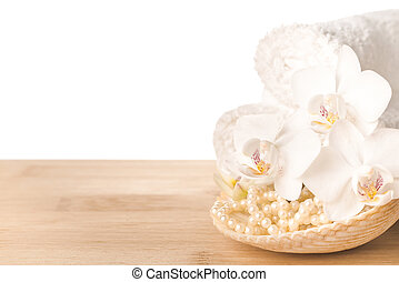 Spa still life of white orchid flower, towel and shell with beads on wood background, isolated