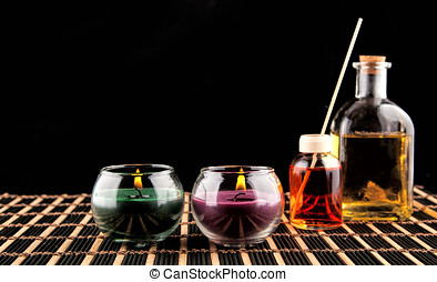 Spa still life with aromatic candles over black background