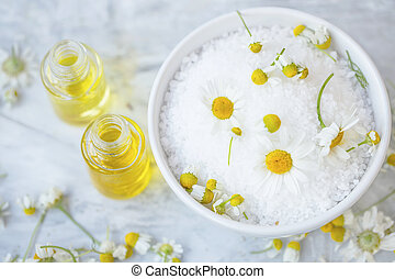Spa still life with chamomile flowers, bath salt and oil bottles