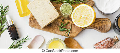 Spa still life with organic ingredients , top view of natural soap, clay, essential oil, rosemary herb, lemon and bath salt on wooden board, organic ingredient for skincare treatments