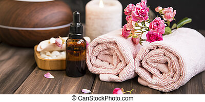 Spa still life with towels, rose oil bottle, rose flowers on wooden background, spa and wellness setting