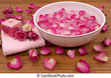 Spa - Fresh bright pink roses, petals, candle, and towel in...