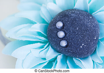 spa stone with drops of lotion surrounded by blue petals