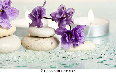 Spa stones and purple flower on white background