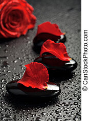 spa stones and rose petals over black background