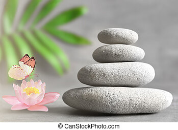 Spa stones with flower lily on light background