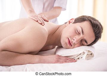 Spa therapy - Close-up. Female masseur doing massage on male...