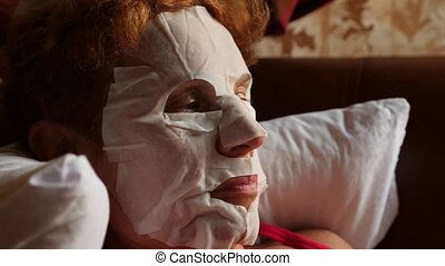 Spa therapy for an elderly woman who receives a face mask....