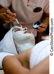 Spa Treatment - A young woman has a facial treatment at a...
