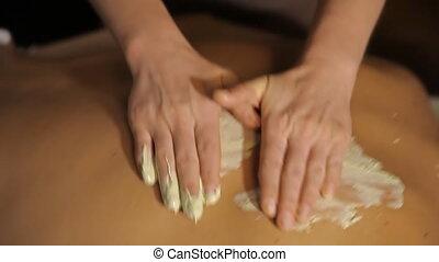 Spa treatment. Applying scrub on a back - Professional...