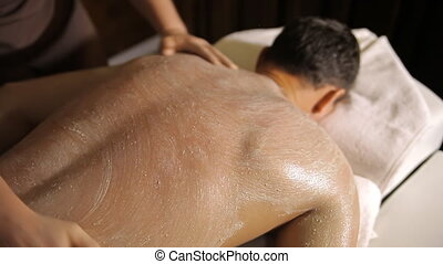 Spa treatment. Applying scrub on back and hands -...