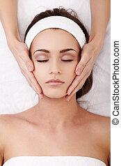 Spa treatment - Beautiful young woman enjoying a facial...