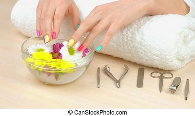 Spa treatment for female hands. Multicolored female finger nails in bath with water and flowers. Nails care and treatment.